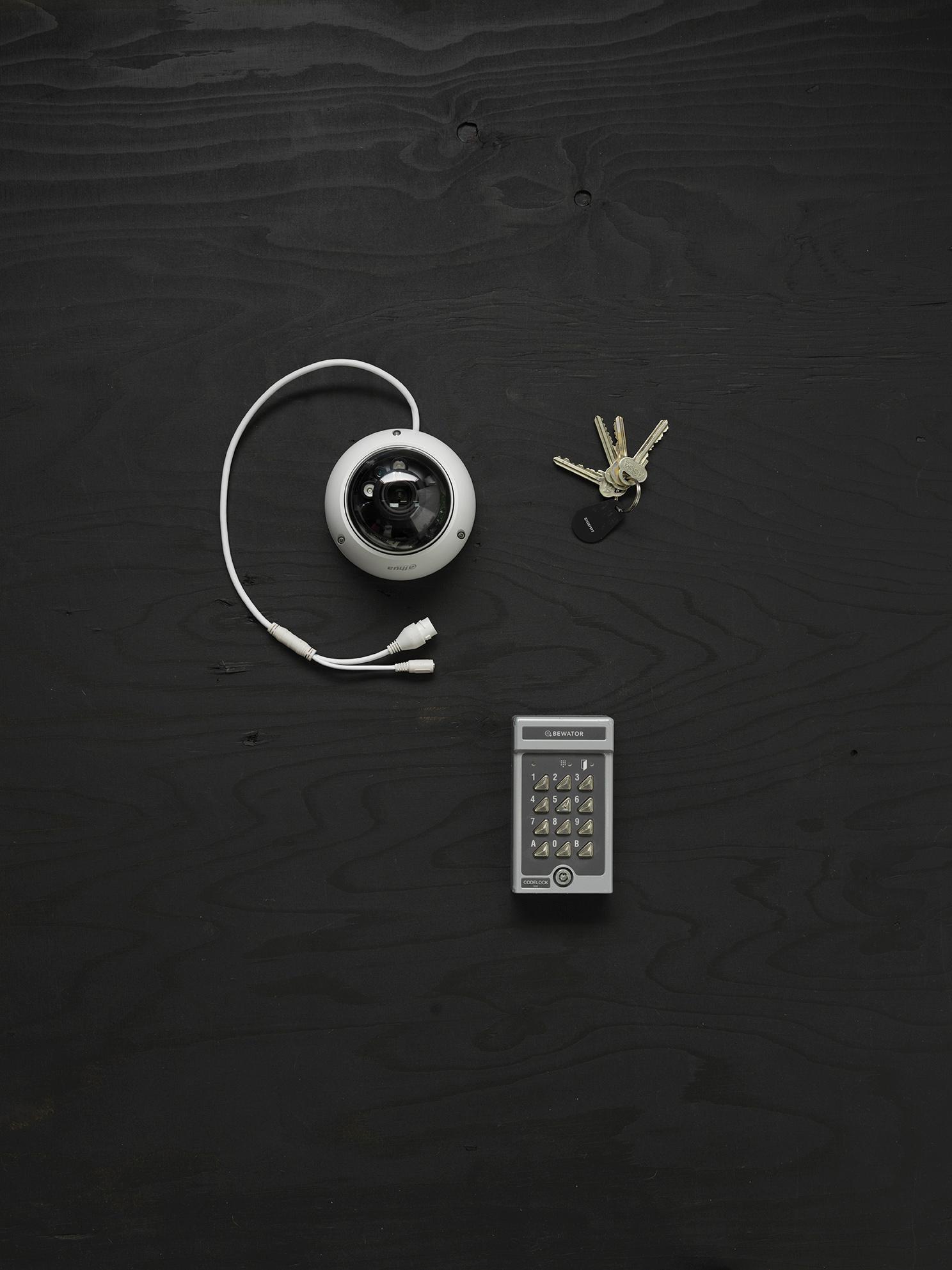 Bild representerar inriktningen låssmed med en övervakningskamera, nycklar och en låskodskombination.
