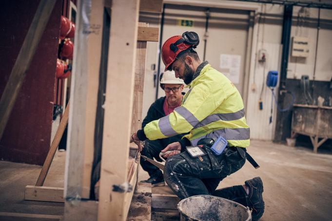 Elev och lärare jobbar i bygghall