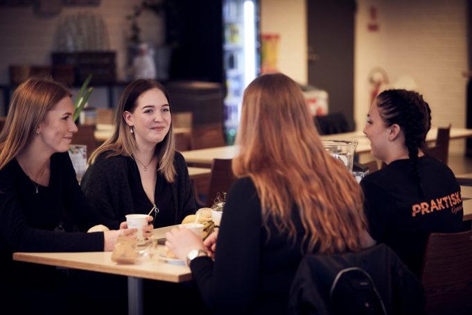 Fyra glada elever äter frukost på skolan