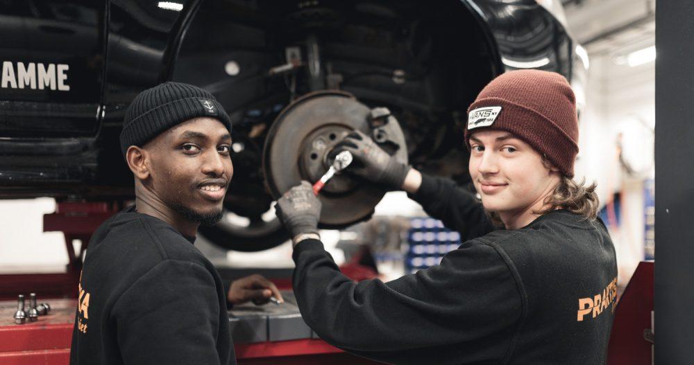 Två elever som mekar med en bil