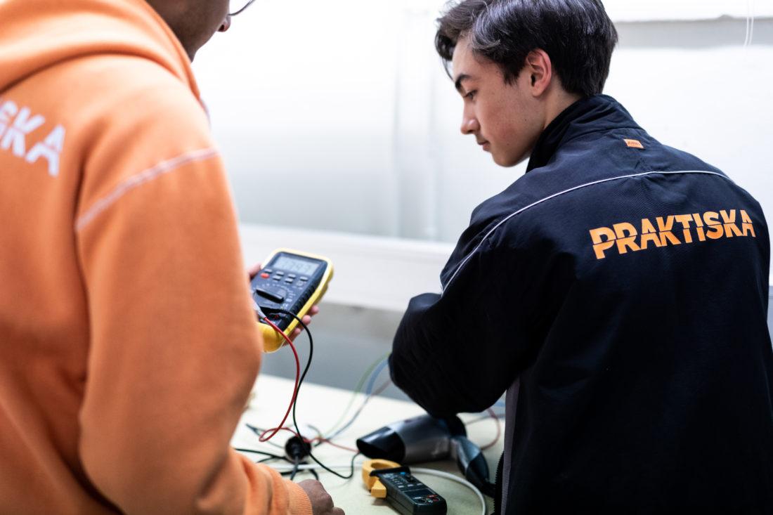 Två elever står och lär som om elenergi, båda har varsin jacka varav en orange och en svart med texten på ryggen