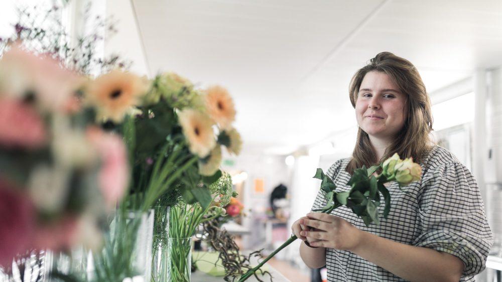 Elev på Floristprogrammet som håller i en ros