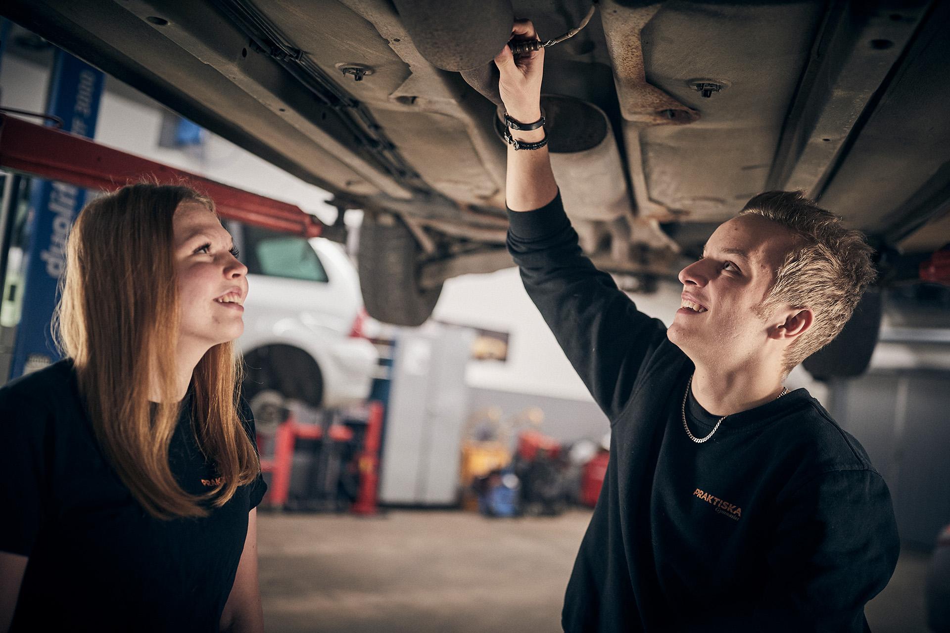 Två elever jobbar i en bilverkstad