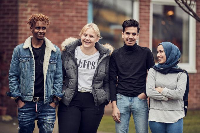 Gruppfoto på fyra elever utan för skolbyggnad