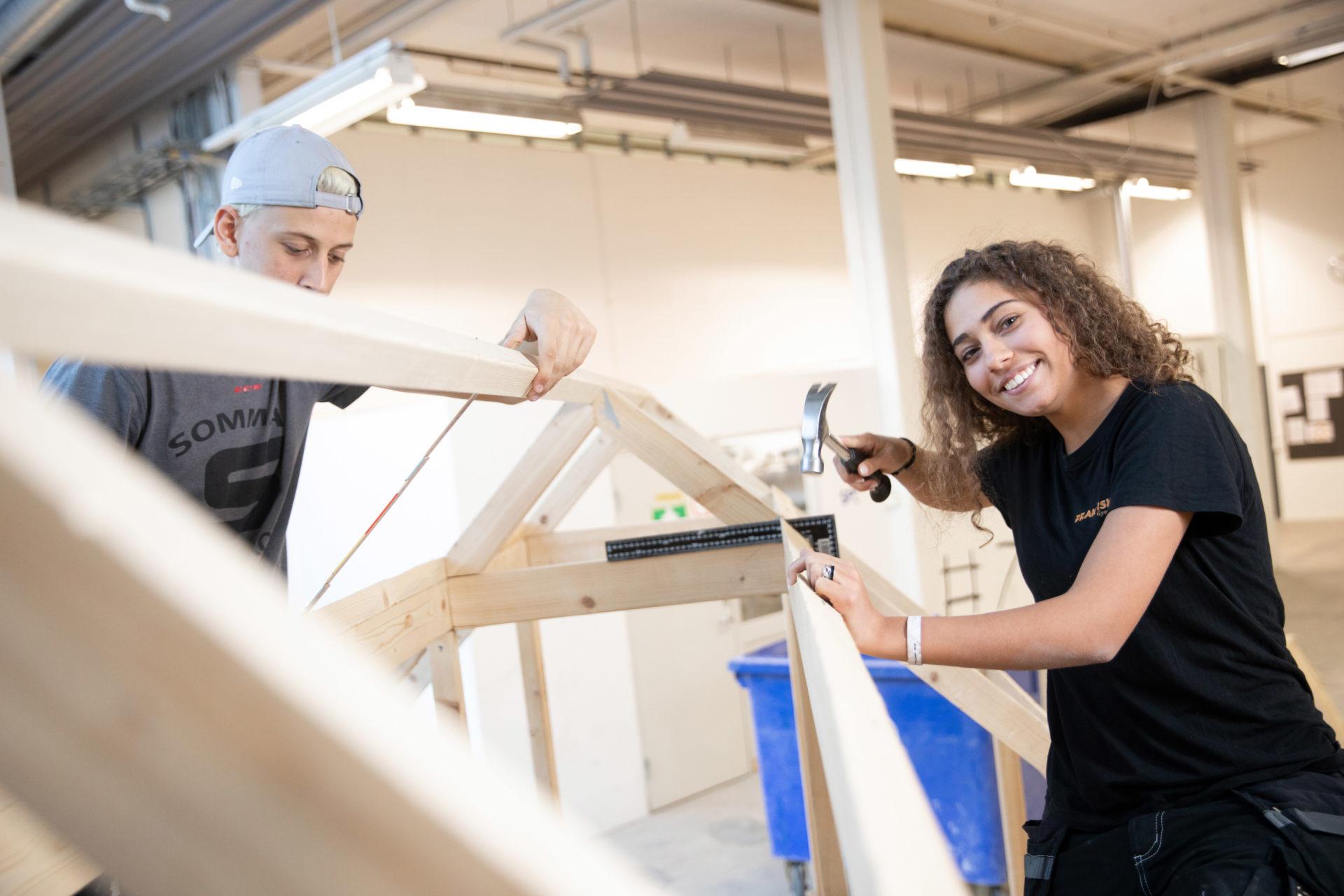 Två elever bygger, en elev ler framför kameran.