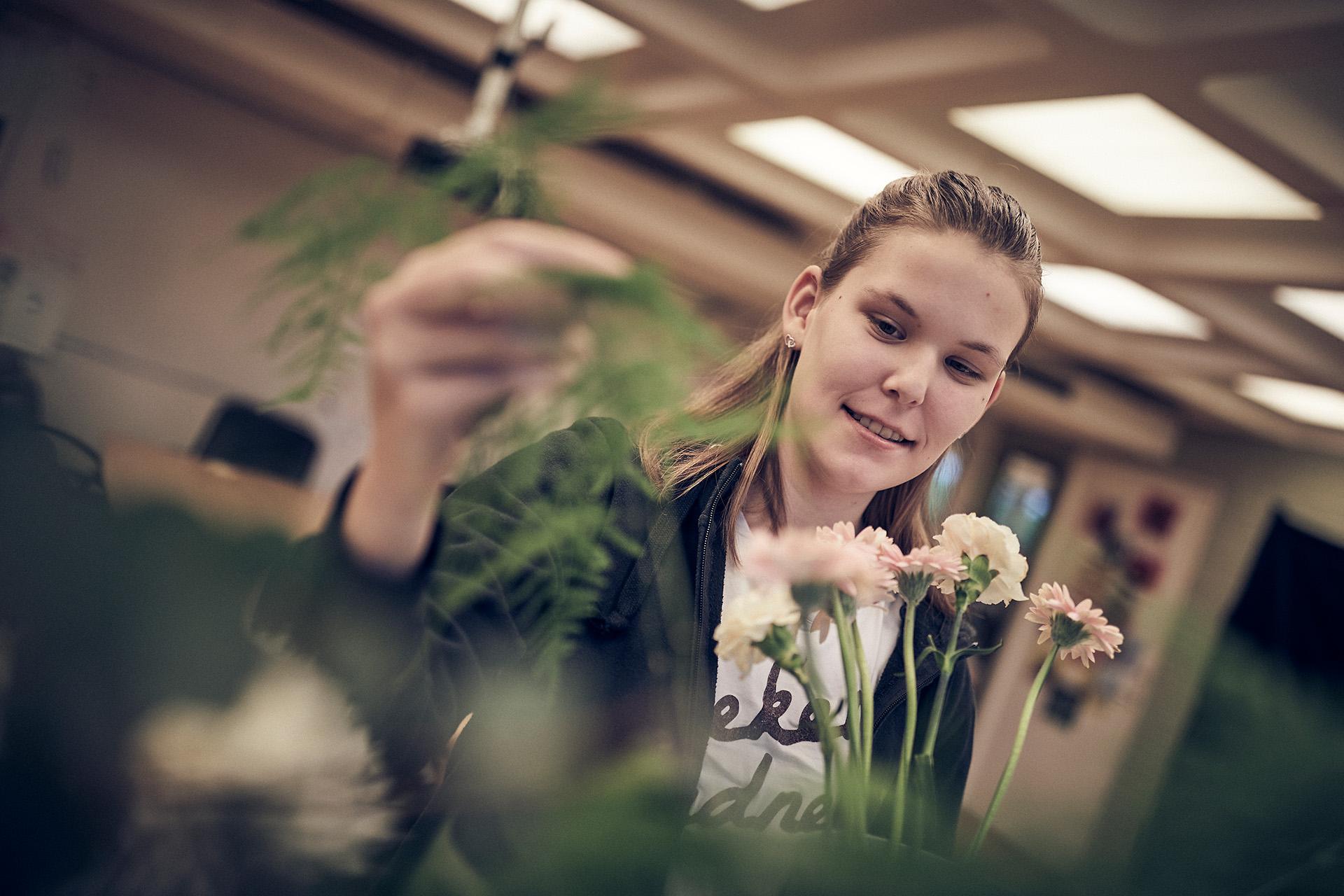 Glad floristelev jobbar med blommor