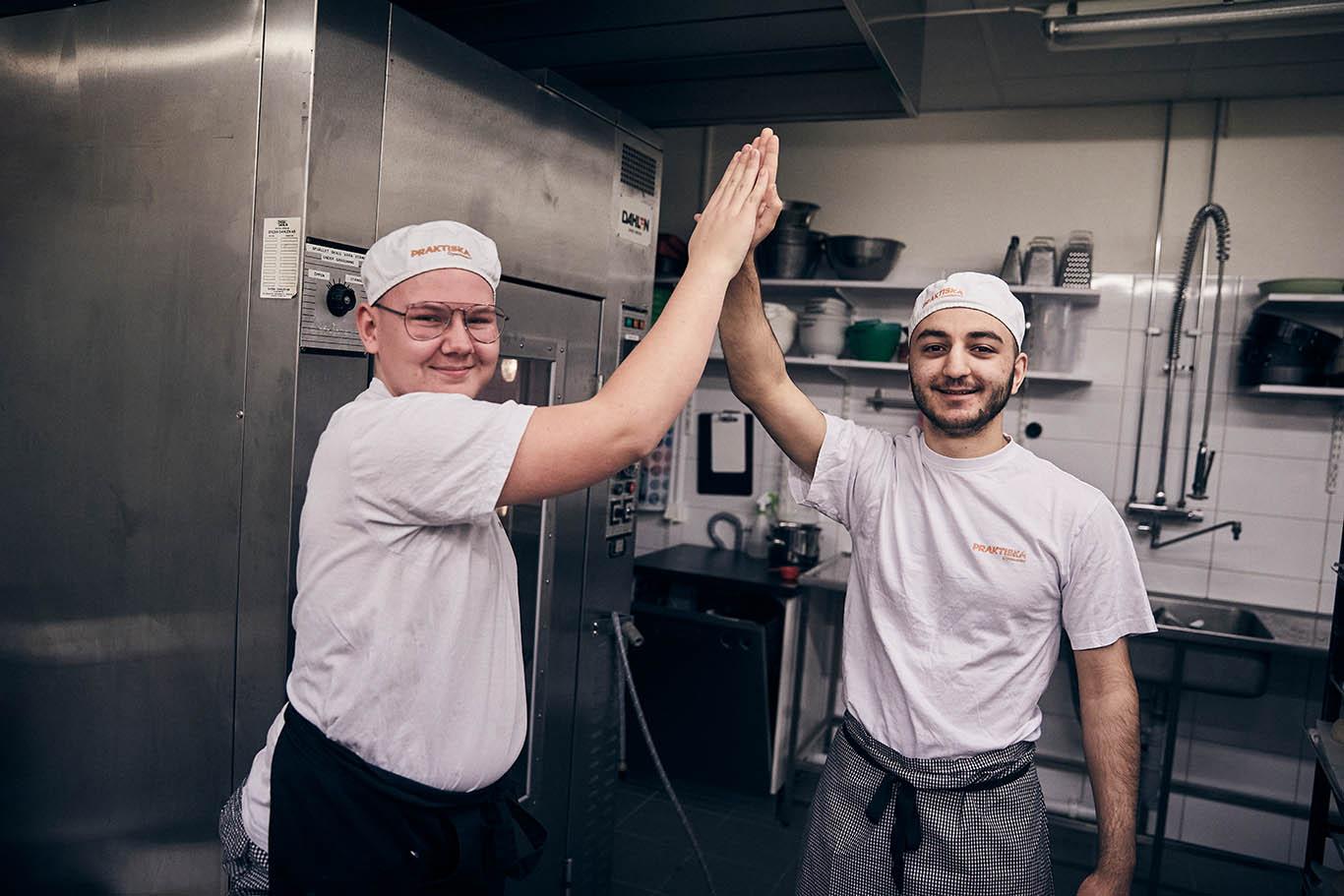 Två killar i restaurangkök gör high-five