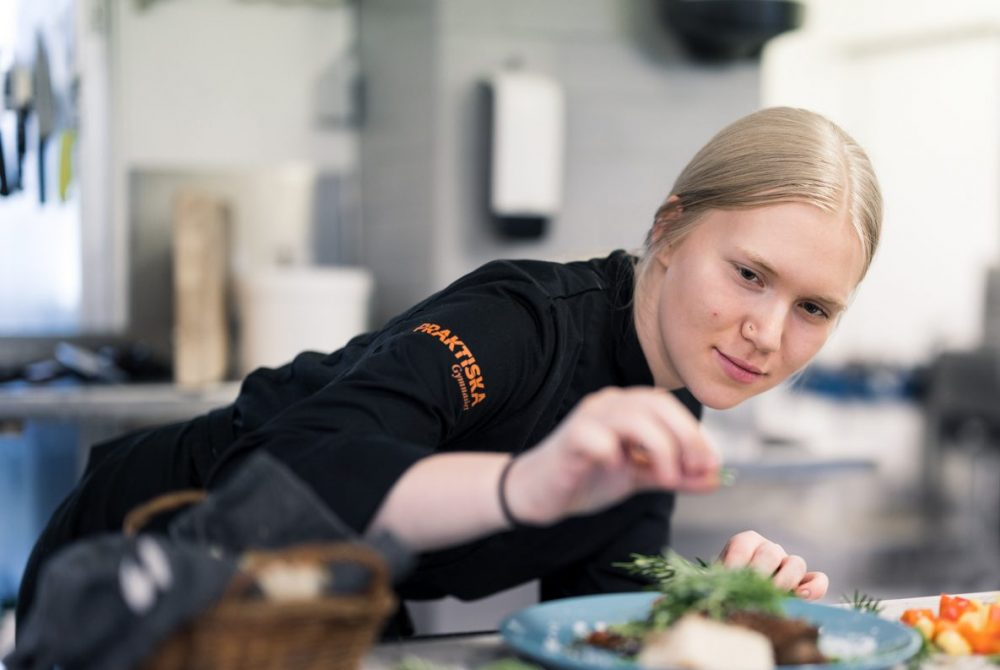 Elev på restaurangprogrammet kryddar en maträtt