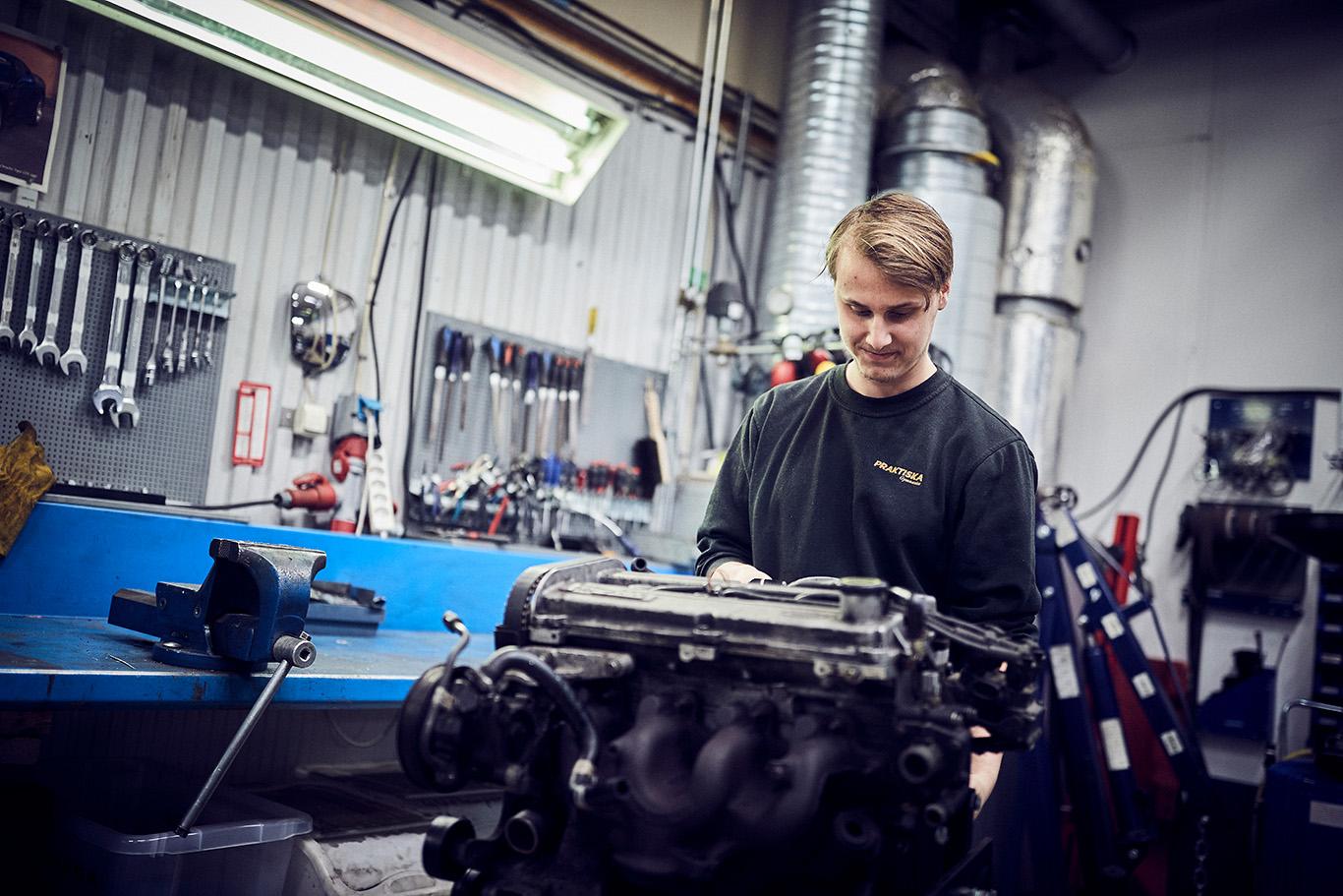 Kille jobbar med motor i bilverkstad