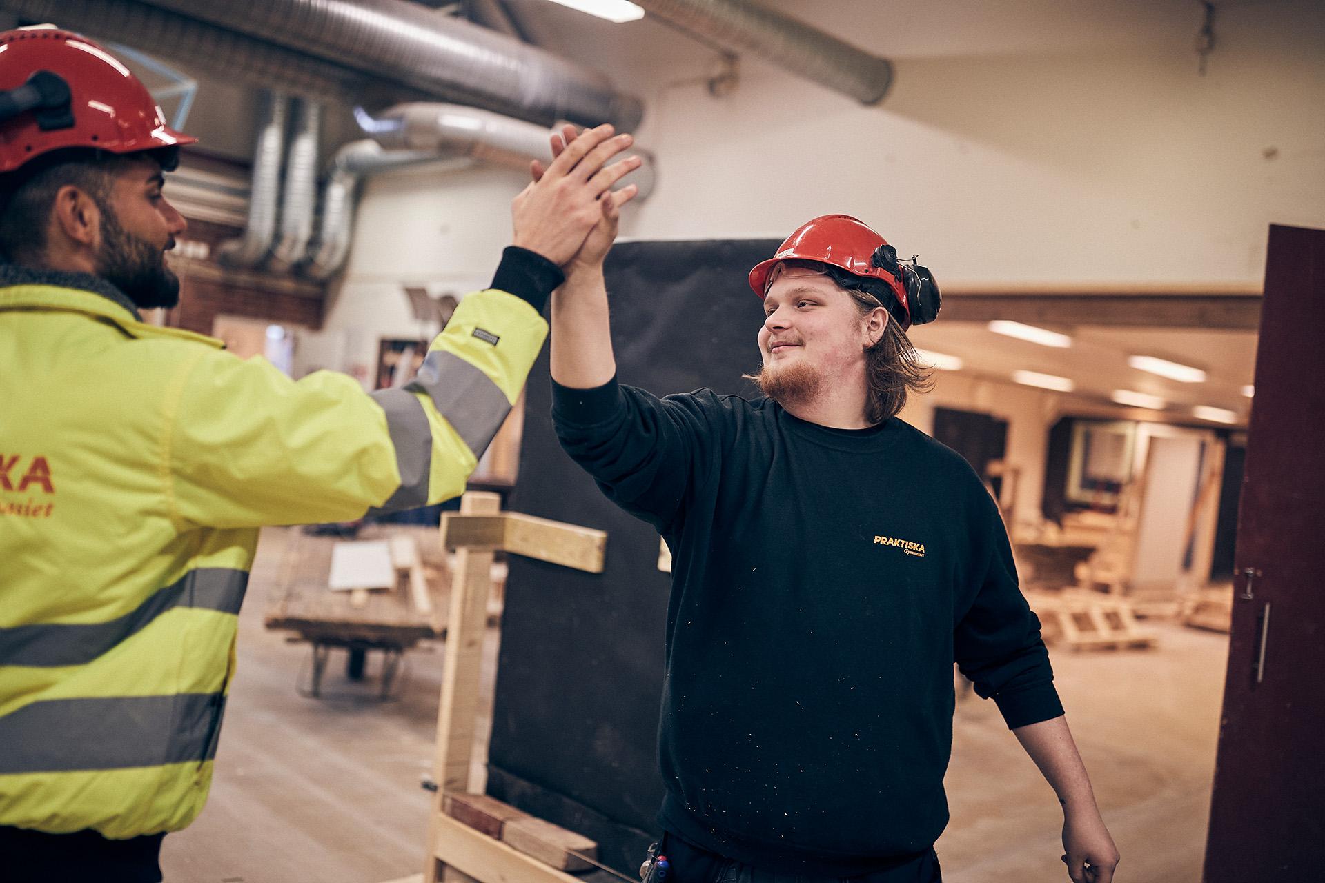 Två killar i bygghall gör high-five