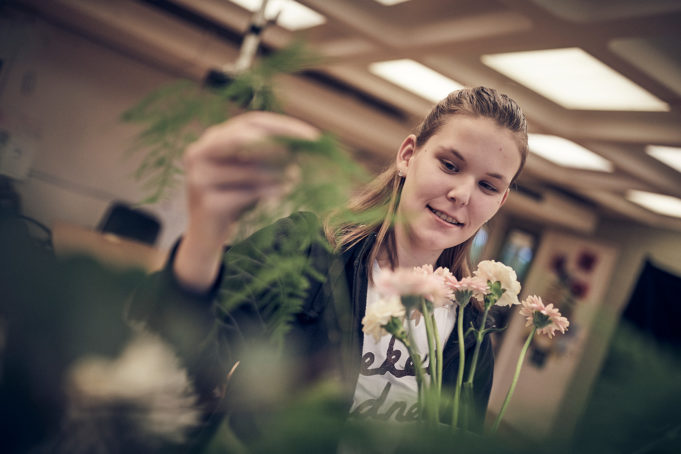 Glad florist elev jobbar med blommor